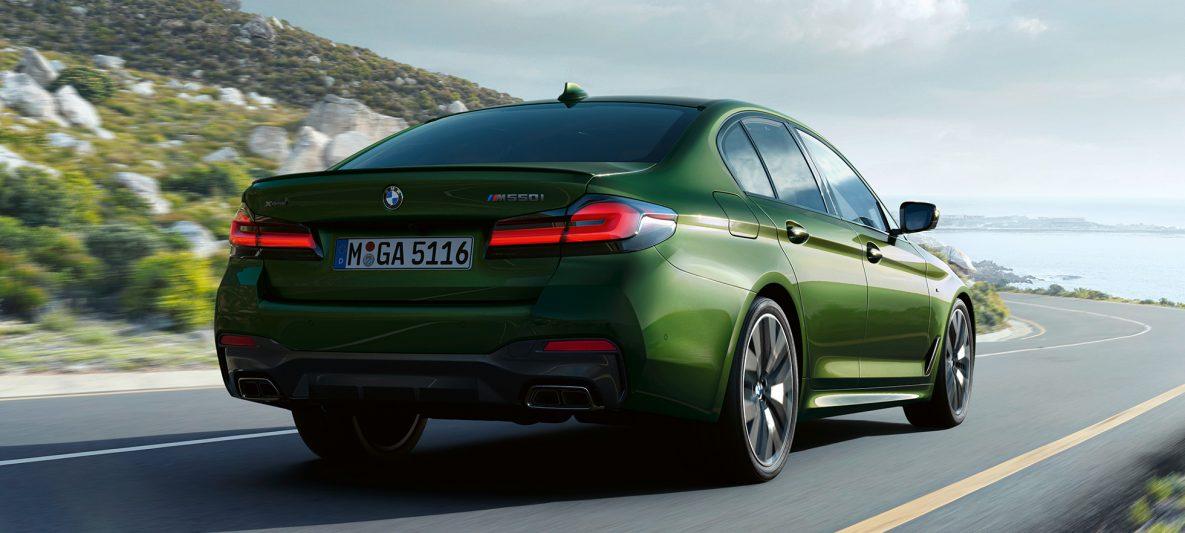 BMW M550i xDrive Limousine G30 LCI Facelift 2020 BMW Individual Verde Ermes metallic Heckansicht fahrend auf Landstraße